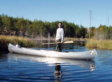 Man standing in canoe on river. A\J AlternativesJournal.ca