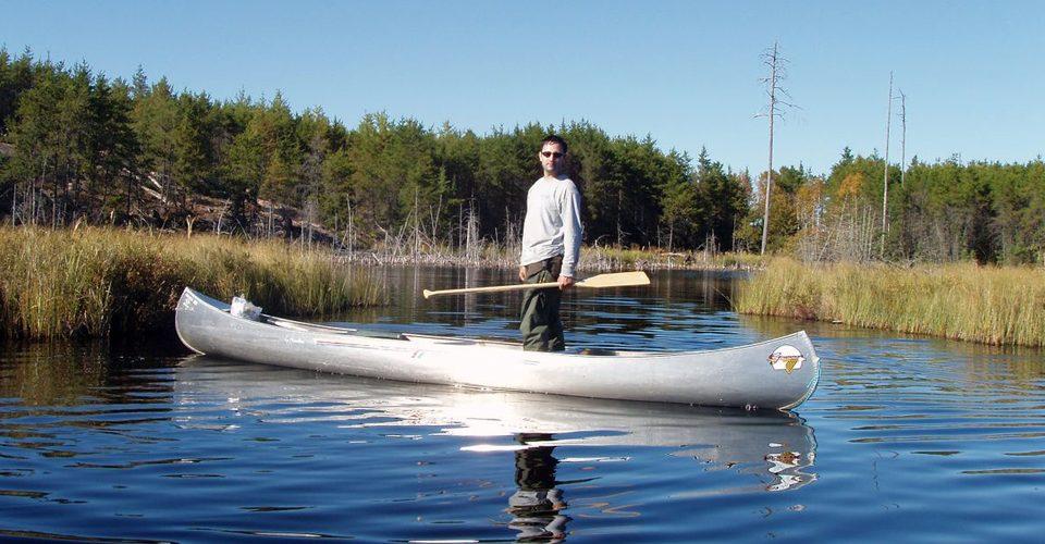 Man standing in canoe on river. A\J AlternativesJournal.ca