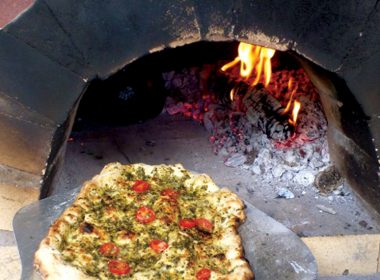 A pesto pizza being placed on an 800°F stone to cook. A\J AlternativesJournal.ca