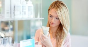 Woman checking for toxic ingredients in beauty products. Alternatives Journal.