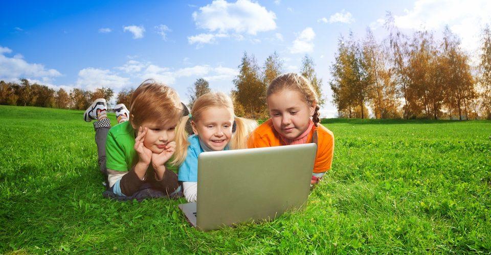 Kids using a laptop outside in a field. Alternatives Journal.