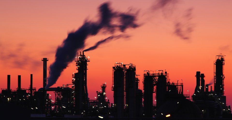 Smoke rising from an oil refinery. Alternatives Journal. A\J.