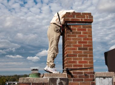 An Ontario SwiftWatch volunteer peers into a chimney.