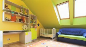 Nursery with shelves, a crib, couch and skylights.
