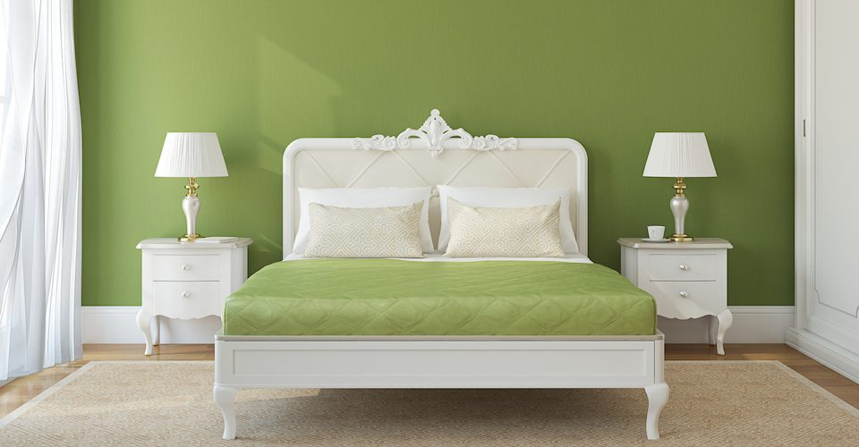 A bed with a green bedspread in front of a green wall.