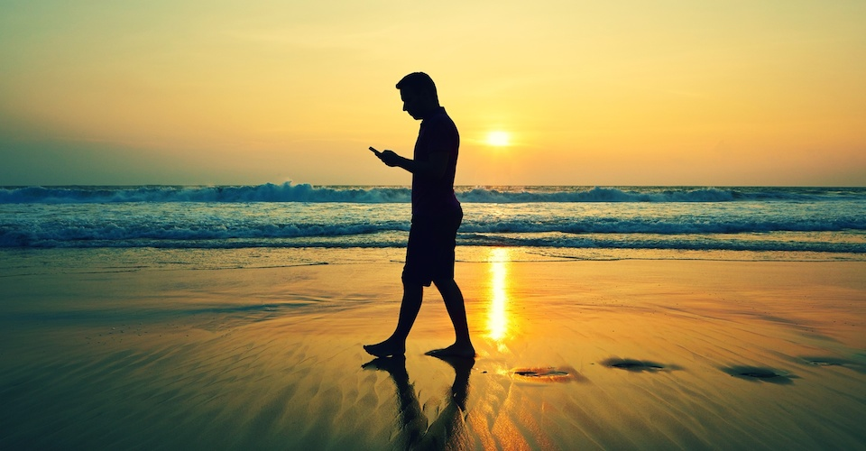 6 Super Summer Apps - man walking on a beach looking at his phone