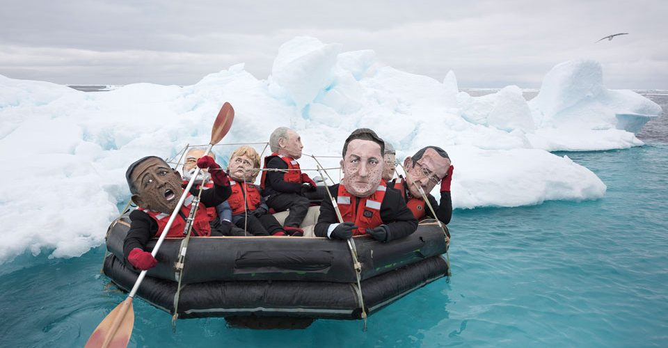 Activists in papier-mâché world leaders' heads flounder in the Arctic Ocean.