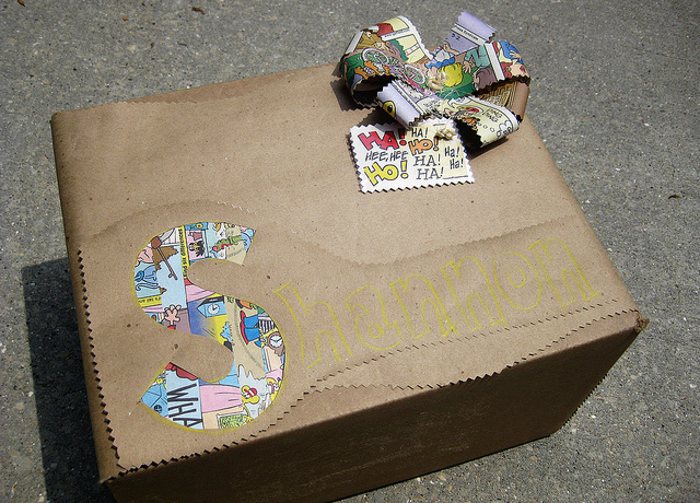 Present wrapped in brown paper with comic bow and cutouts revealing comics underneath.