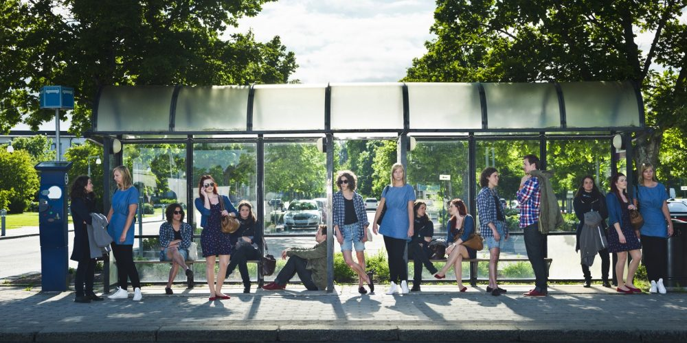 (Photo: a group of people waiting at a bus stop)