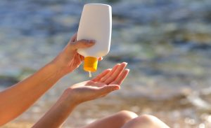 Woman putting sunscreen from a bottle on the beach