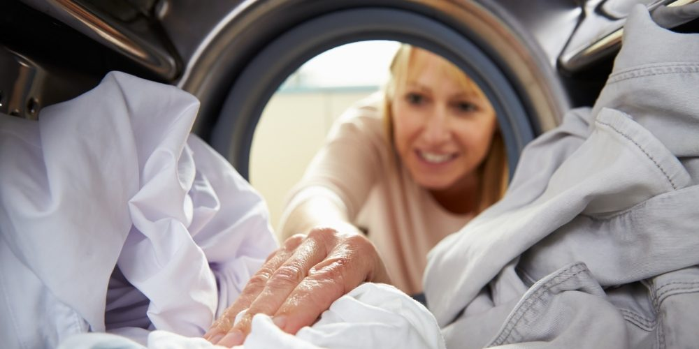 (Photo: a woman reaching into a washing machine)