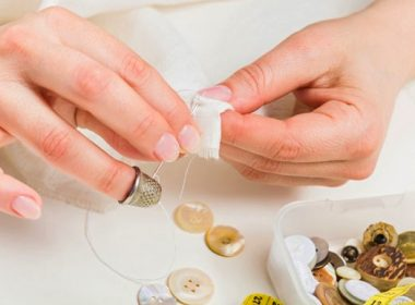 (Photo: a woman sews a button on fabric)