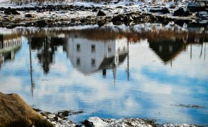 (Photo: a reflection of a village in a body of water)