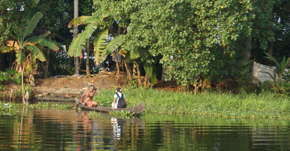 A man paddles a girl to school on the backwaters of Kerala, India