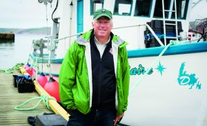 David Miller stands on the dock near a fishing boat