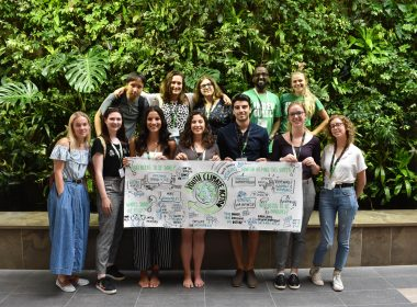 Students holding a YACC sign in front of a green wall
